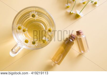 Chamomile Tea, Tincture Or Oil In Bottles And Chamomile Flowers Top View