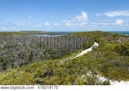 The Aerial View Of Grand Turk Island Rural Landscape With A Car Traveling Along The Road (turks And
