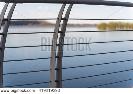 Metal Gray Fence, Thick Horizontal Bars And Vertical Double Plates, Embankment, Blue River, Blurred