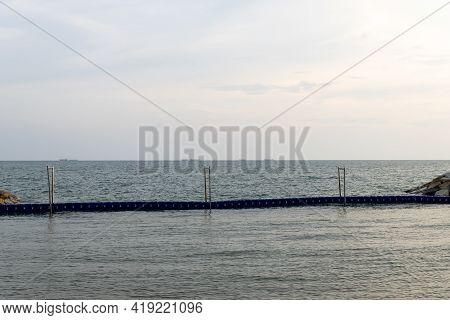 Wave Barrier Tank. Beach Wave Barrier. Beach Broken By Sea Waves.