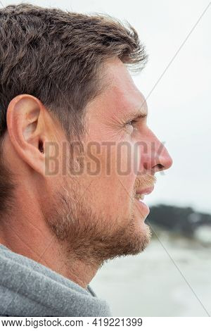 Portrait Of A Handsome Young Man Walking Along The Ocean Beach In The Evening. Traveling People Conc