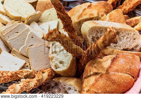 Basket Of Bread With Different Types Of Cheese On The Table