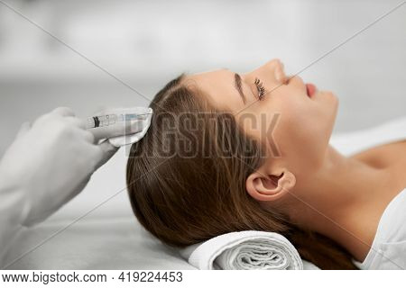 Side View Of Young Brunette Woman On Procedure For Improvements Hair With Special Injection. Concept
