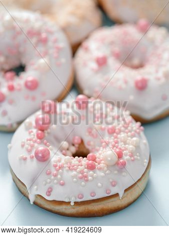 Delicious Tender Donuts Glazed White Glaze And Sprinkled With Pink Pearl Dressing. Idea Decorating D