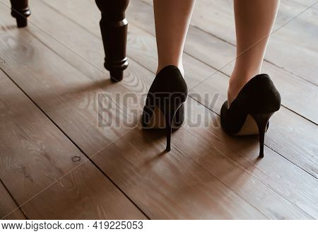 Little Girl Stay Back In Big Adult Mother Black High Heels Shoes Near Chair At Wooden Floor, Imitati
