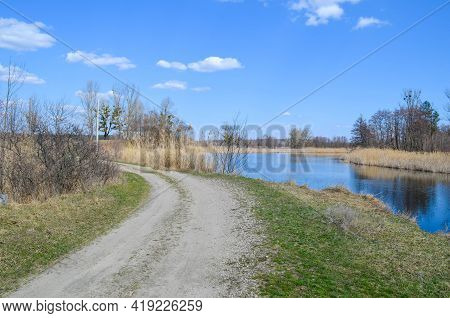Coutryside Road Going Past River And Through The Meadow. View On The Rural Nature River Trees And Bl