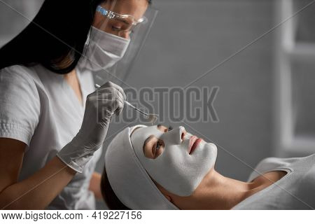 Side View Of Young Beautiful Woman Lying On Procedure For Cleaning Face In Beautician In Protective