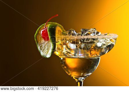 Cocktail Garnished With Cherry And Lime On A Yellow Background.