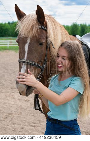 Young Caucasian Woman On Brown Horse Back. Horseback Riding As Hobby In Paddock On Woods. Green Tree