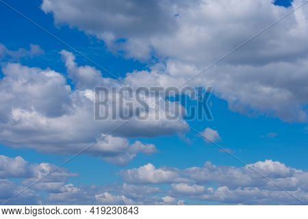 A lot of white fluffy cumulus clouds on bright summer blue sky. Cloudscape, overcast.