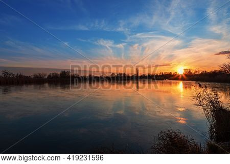 Beautiful Landscape By The Pond. The Sun Is Setting Behind The Pond. Blue Sky And White Clouds Are R