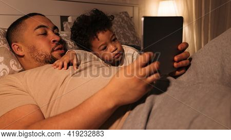 Close Up View Of Man And Boy Lying On Bed And Reading Book On Digital Tablet. Father And Son Looking