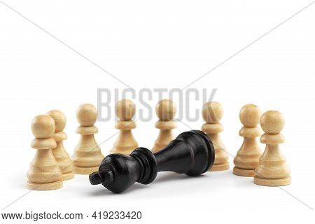 The Black King Lies In Front Of A Row Of White Pawns On A White Background. White Wooden Chess Piece
