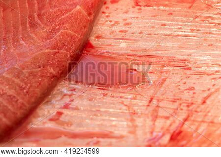 Sliced Piece Of Fresh Tuna Fish With Bloody Blood Trail. Traditional Healthy Sea Food From Seafood M