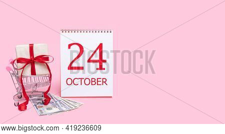 24th Day Of October. A Gift Box In A Shopping Trolley, Dollars And A Calendar With The Date Of 24 Oc