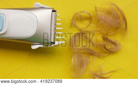 Haircut Machine Is Insulated On A Yellow Background, Next To A Strand Of Trimmed Hair. Hair. A Haird