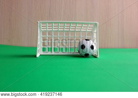 Football. A Football In A Small Gate On A Gray Background. Mini Football. Sports Game. The Ball Is I