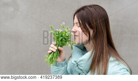 Beautiful Young Woman Sniffing Wild Flowers. A Bouquet Of Flowers In Female Hands. Spring And Spring
