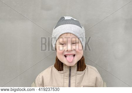 A 4-year-old Boy Shows His Tongue. The Child Smiles And Shows Tongue