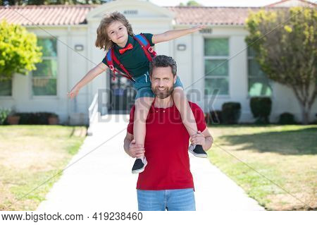 Father And Son Walking Trough School Park. Father Giving Son Piggyback Ride After Come Back From Sch