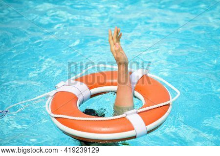 Safety Equipment. Life Buoy Or Rescue Buoy Floating On Water. Drowning Person.