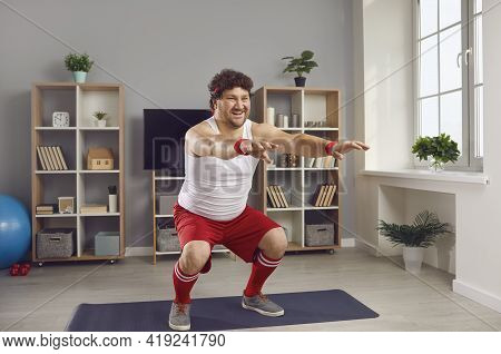 Funny Chubby Man In Retro Activewear Doing Squats During Fitness Workout At Home