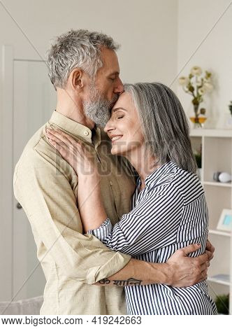 Smiling Mid Age Older Couple Hugging And Kissing Standing At Home. Happy Senior Adult Mature Classy