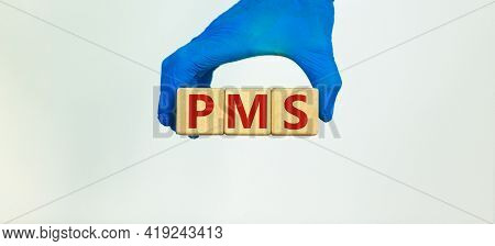 Medical And Pms, Premenstrual Syndrome Symbol. Hand In Blue Glove Holds Wooden Cubes With The Word '