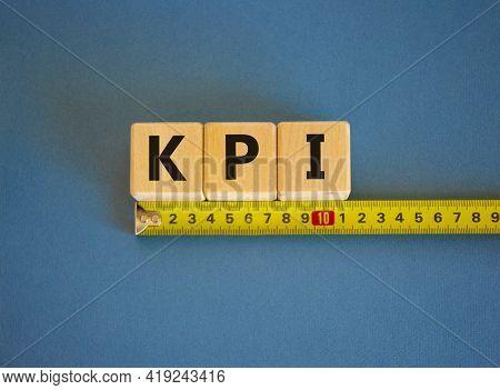 Kpi - Key Perfomance Indicator Symbol. The Word Kpi, Key Perfomance Indicator On Cubes Arranged Behi