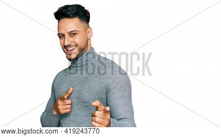 Young arab man wearing casual clothes pointing fingers to camera with happy and funny face. good energy and vibes.