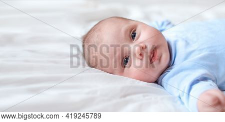 Close-up Portrait Of A Beautiful Baby On White. Head And Face. Newborn Baby Lying On Side And Looks