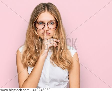 Beautiful young caucasian girl wearing casual clothes and glasses asking to be quiet with finger on lips. silence and secret concept.