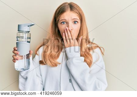 Beautiful young caucasian girl wearing sportswear drinking bottle of water covering mouth with hand, shocked and afraid for mistake. surprised expression
