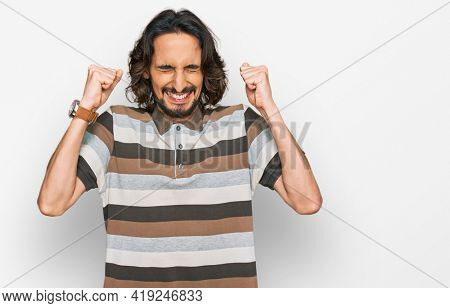 Young hispanic man wearing casual clothes excited for success with arms raised and eyes closed celebrating victory smiling. winner concept.