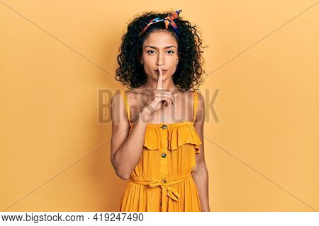 Young latin girl wearing summer dress asking to be quiet with finger on lips. silence and secret concept.