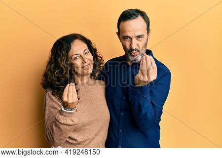 Middle age hispanic couple wearing casual clothes doing money gesture with hands, asking for salary payment, millionaire business