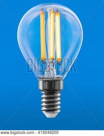 Energy Efficient Led Filament Light Bulb Glowing Isolated On Blue Background.