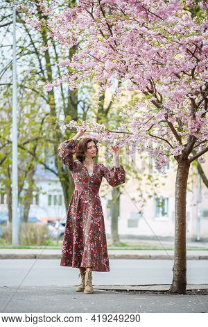 In The Spring, A Woman Walks Along A Blooming Street With Sakura Trees. A Girl In A Long Silk Elegan