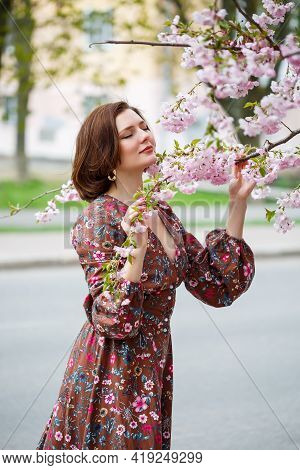 A Woman Walks Along A Spring Street. The Girl Enjoys The Scent Of A Blossoming Tree. Beautiful Woman