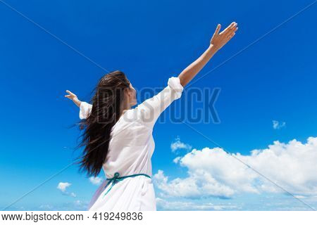 Young woman with raised hands and cloudy sky background