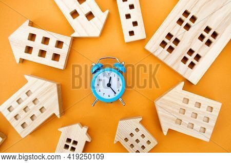 A Blue Alarm Clock And Many Wooden Houses Around. Mortgage And Loan Concept. Real Estate And Risks.