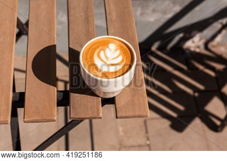 White Cup Of Cappuccino Or Flat White With Latte Art On Milk Foam On Wooden Table Of Cafe Veranda Ba