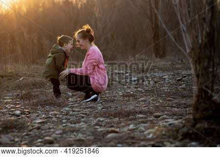Beautiful Mother Playing With Her Son In Nature Against Sunset. Mother's Day Concept