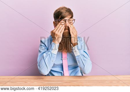 Young irish redhead man wearing business shirt and tie sitting on the table rubbing eyes for fatigue and headache, sleepy and tired expression. vision problem