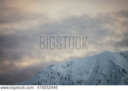 Minimal Alpine Landscape With Snowy Mountain Range On Background Of Sunset Or Sunrise Cloudy Sky Of