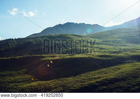Beautiful Sunny View To Green Hills And Mountain In Sunlight. Scenic Nature Landscape With Lens Flar