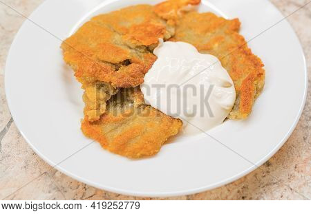 Potato Pancakes With Sour Cream On Ceramic White Plate Closeup. Poor Country Cheap Food.