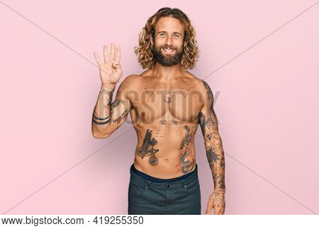 Handsome man with beard and long hair standing shirtless showing tattoos showing and pointing up with fingers number four while smiling confident and happy.