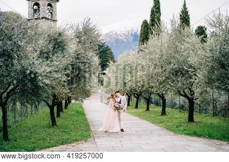Newlyweds Walk In An Olive Grove Against The Background Of An Old Tower With Bells On Lake Como. Sid