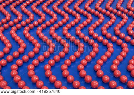 Background From Red Plastic Beads On A Transparent Fishing Line. The Beads Are Arranged In A Vertica